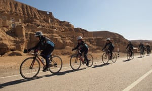 The Afghan Women's National Cycling Team passes mud dwellings on the highway through the mountains of Afghanistan's Bamiyan Province.