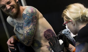 A man gets tattooed at The Great British Tattoo Show at Alexandra Palace in 2014. y