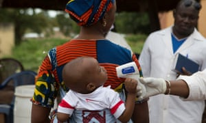 A health worker checks the temperature of a baby entering Mali from Guinea.