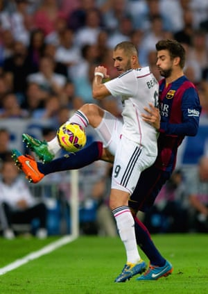 Gerard Pique and Karim Benzema tussle for the ball