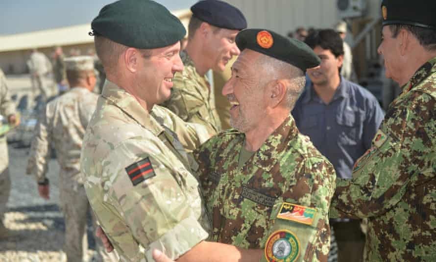 British and Afghan soldiers embracing each other during the handover ceremony of Camp Bastion in Afghanistan.