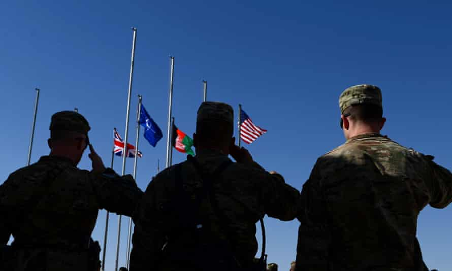 Soldiers salute as the British, Nato, Afghan and US flags are seen on their masts during a handover ceremony before the British and US military withdrawal from Camp Bastion.