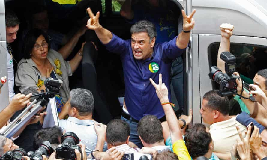 Aécio Neves makes victory signs after voting in the Brazilian presidential election run-off in Belo Horizonte.
