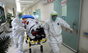 Medical workers wearing protective suits handle a protective stretcher as they conduct a training exercise on dealing with suspected Ebola case.