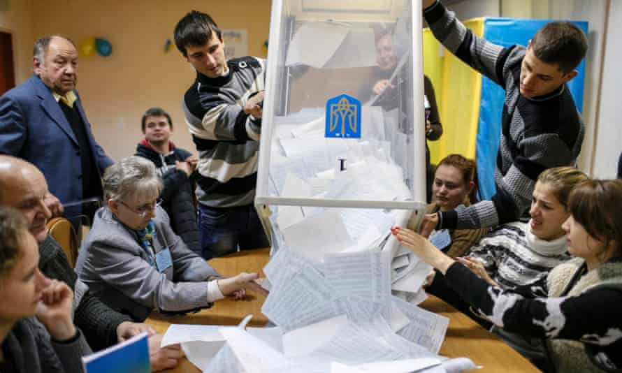 Members of a local electoral commission empty a ballot box at a polling station after voting day in Kiev.