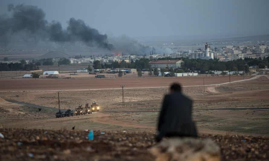 A man watches US air strikes aimed at Isis forces from a hill in Sanliurfa province of Turkey