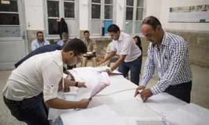 Electoral workers count ballots at a polling station in Tunis.