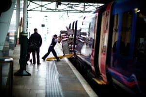 A crew member loads the refreshment trolley on to the train