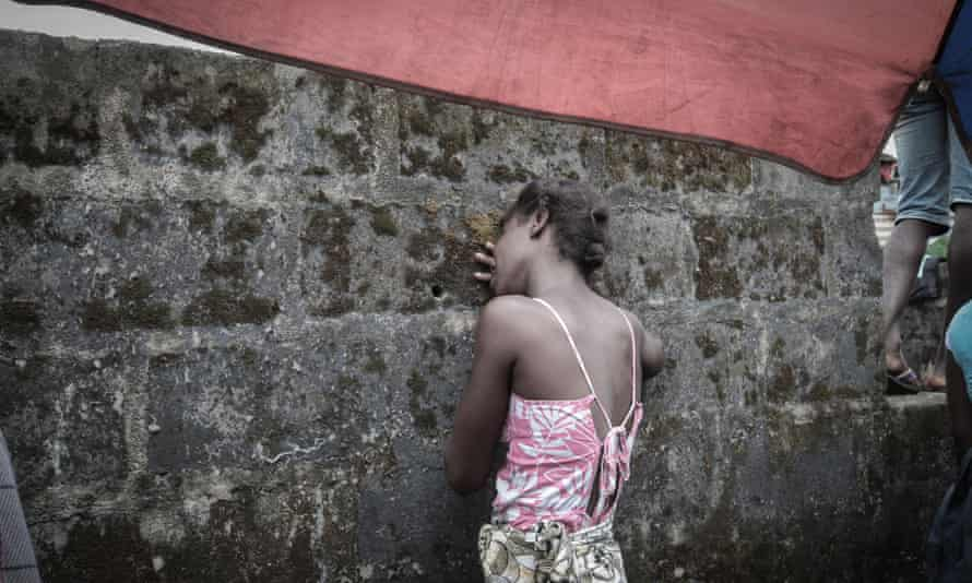 The daughter of an Ebola victim grieves in Monrovia, Liberia.