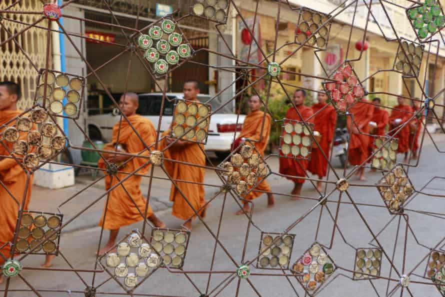 Monks collect morning alms outside the Maek Maek gallery, in front of sculpture by Battambang artist Mao Soviet.