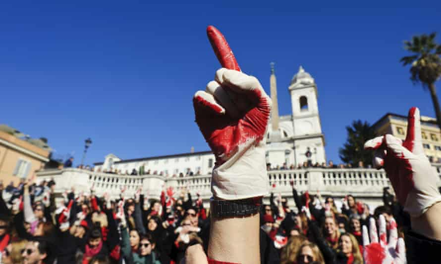 Women hold up their hands at a rally to end violence towards women in Italy.