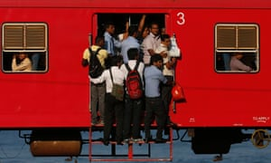 People hang onto a crowded train as they travel to Colombo. Sri Lanka.