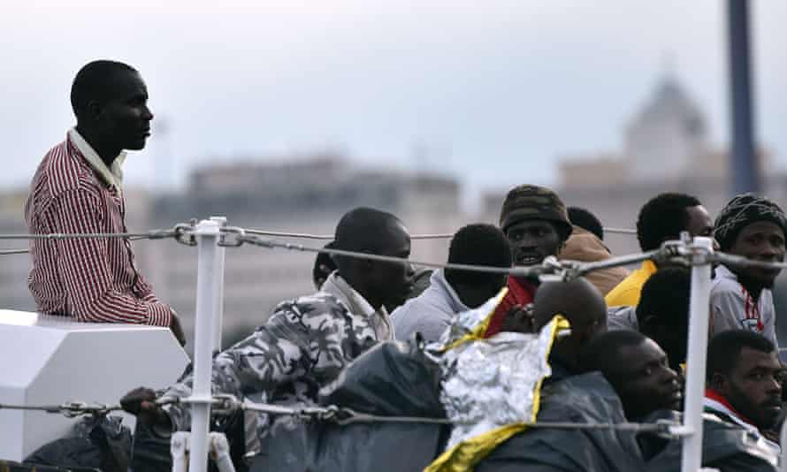 Rescued migrants wait to disembark in Palermo, Italy