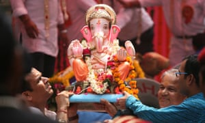 Ganesh is carried by devotees in a religious procession in New Delhi