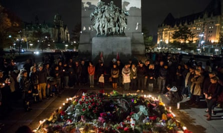 The Tomb of the Unknown Soldier at the National War Memorial is surrounded by people during a candlelight vigil in Ottawa.