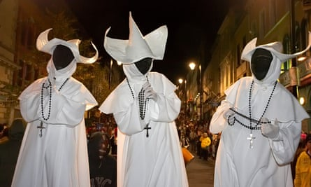 Three people dressed as ghostly nuns with black faces, rosary beads and crosses in Derry, Ireland