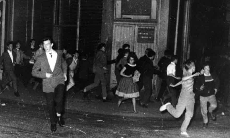 Teddy boys and girls run through Blenheim Crescent, Notting Hill during the race riots, September 1958.
