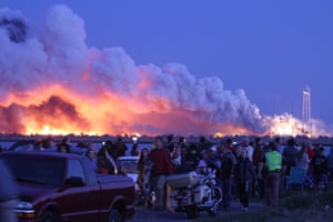 People watching the rocket launch turn to leave as smoke and flames engulf the sky