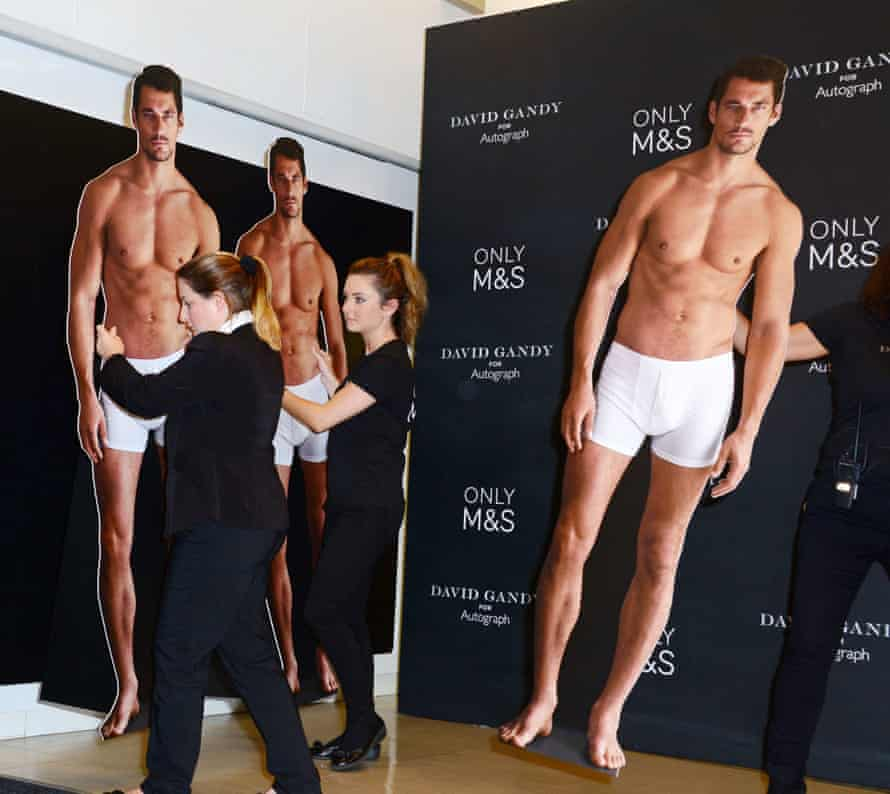 Assistants carry lifesize cardboard cut-outs of David Gandy