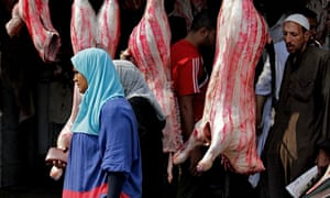 An Egyptian woman walks past meat displayed for sale
