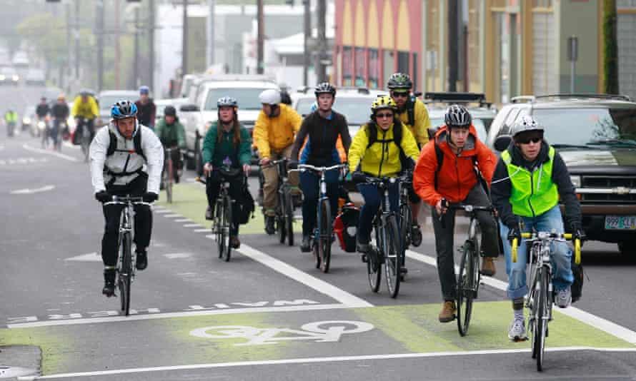 Bike commuters travel down along a street, in Portland, Oregon