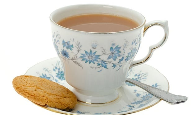 Classic cup of tea on saucer with biscuit