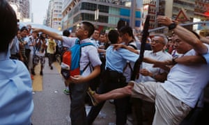 A pro-democracy protester  argues with an anti-Occupy Central protester  while being kicked by another anti-Occupy Central protester  at Hong Kong's  Mongkok district,