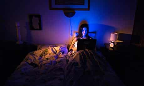 Young woman using the laptop in bed at home