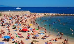 People enjoy the sunshine on a beach in Antibes, France.