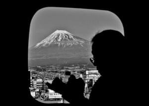 On a Kyoto bound shinkansen, a salaryman reads as the iconic mount Fuji passes by.