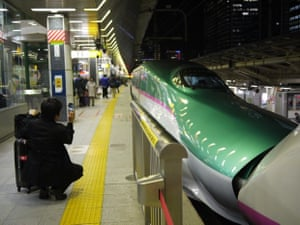 'A businessman takes a snapshot of a green Shinkansen at Tokyo station. The nose of this train has swiveled open to couple with another train to make the journey north from Tokyo.'