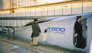 Tokyo-Kyoto Bullet train awaiting passengers. 'An excited Japanese boy just has to touch the sleek lines of the bullet train we were about to board.'