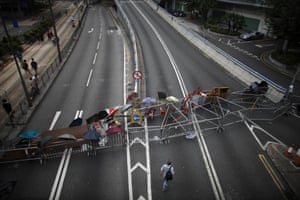 Here, a man walks by a barricade built by the  protesters to block areas around the government headquarters building