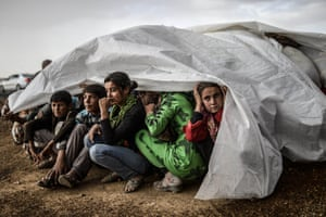 And, in another photograph by Bulent Kilic, Syrian Kurds take cover from the rain in Suruc after crossing the border