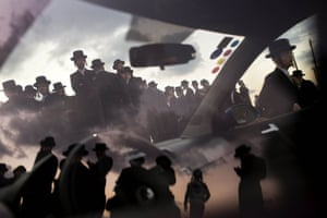 Ultra-Orthodox Jews are reflected in a car window as they participate in a Tashlich ceremony in Herzeliya, Israel. Tashlich, which means 'to cast away' in Hebrew, is the practice in which Jews symbolically cast away their sins by throwing a piece of bread, or similar food, into the water before the Jewish holiday of Yom Kippur