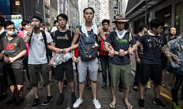 Pro-democracy protesters link arms to protect a barricade from counter-demonstrators in Hong Kong