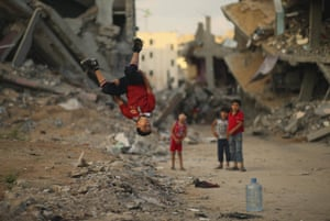 In this photograph by Mohammed Salem, a regular contributor to the twenty photographs of the week, a Palestinian boy practises his parkour skills near the ruins of houses, which witnesses said were destroyed during the seven-week Israeli offensive, in Gaza