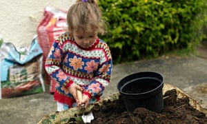 A Six year old Girl Filling up a Pot with Compost