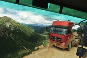 Being carried over the 5050m high Chola Pass, China, by a lorry who soon suffered from a flat tyre.