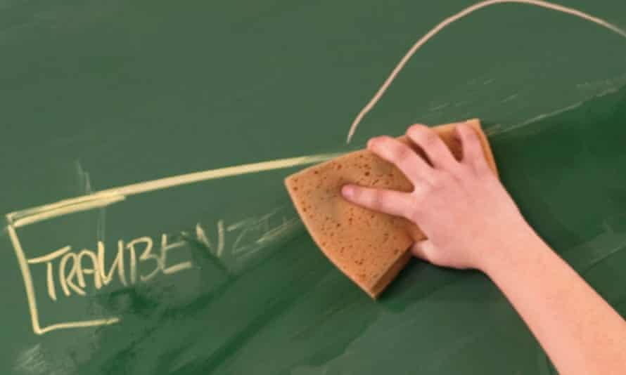 Girl wipes text off blackboard