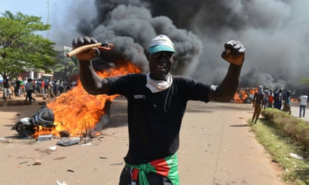 A man stands in front of a burning motorbike in Ouagadougou