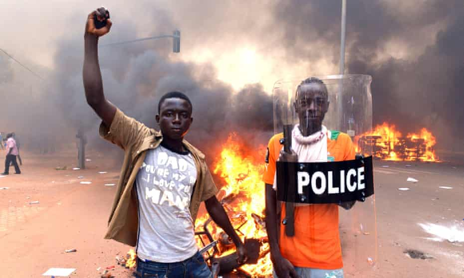 Two young men stand in front of a bonfire outside the parliament building in Ougadougou, Burkina Faso.