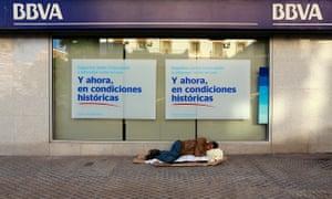 A homeless man sleeps outside a BBVA bank in Seville
