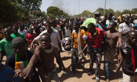 Anti-government protesters carry the injured in a crowed in Ouagadougou, October 30, 2014.