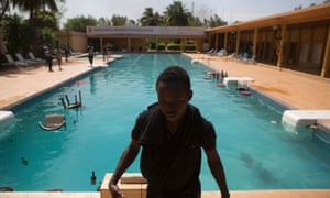 A protester stands in front of a hotel pool, where members of the parliament were said to be staying in Ouagadougou, October 30, 2014.