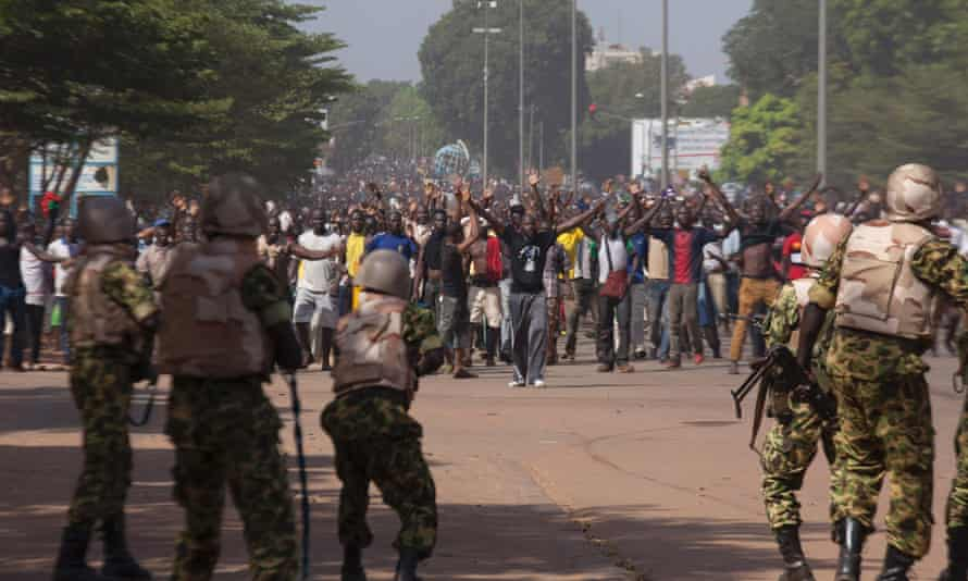 Soldiers attempt to stop anti-government protesters from entering the parliament building in Ouagadougou, October 30, 2014.