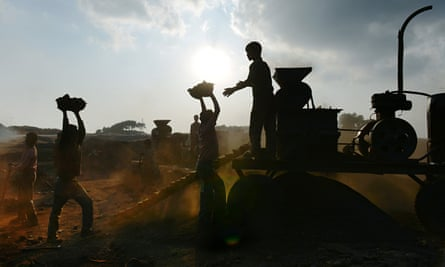 Children carry coal in baskets to a crushing machine at a roadside depot in the Indian state of Megh