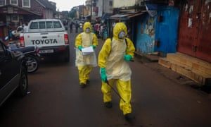 Health workers walk to pick up a four-month-old baby victim of Ebola in central Freetown.