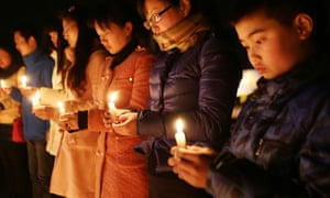 people hold candles at a vigil for victims of the kunming mass stabbing