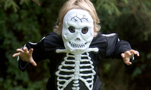 boy tries to scare in a skeleton halloween outfit